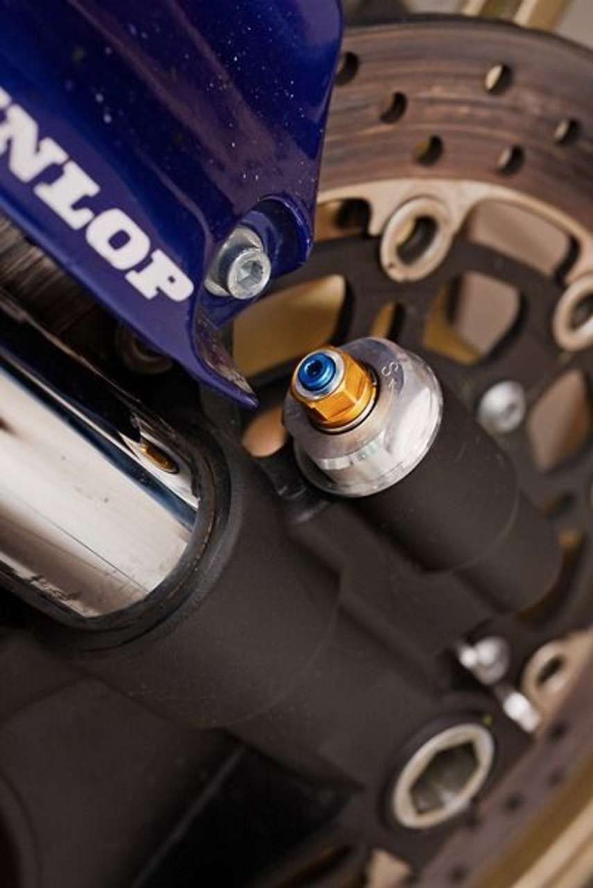 Die Druckstufe (hier die blaue Schraube am Ausgleichsbehälter) dämpft die Einfedergeschwindigkeit und verhindert ein Springen der Räder. Allzu harte Einstellung provoziert rutschende Reifen. Im Idealfall bleiben 5 bis 10 Millimeter Federwegsreserve, bevor die Gabel durchschlägt.