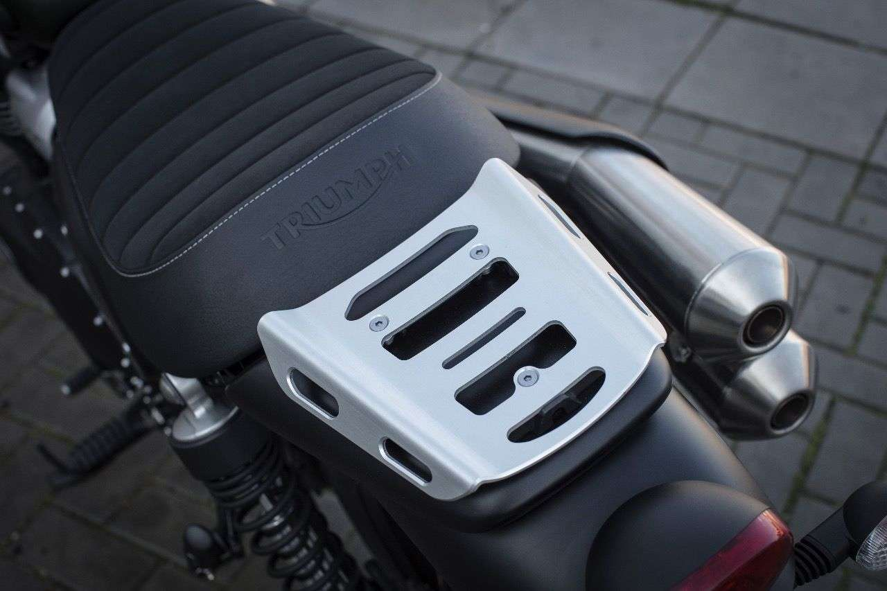 Der kleine und nicht besonders bequeme Soziussitz der Triumph Scrambler kann ruckzuck gegen einen serienmäßig mitgelieferten Alu-Gepäckträger getauscht werden.